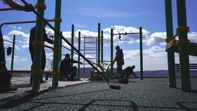 Een groep arbeiders behandelt de Speelplaats met rubberkruimel met een laag die wordt bedekt die stock footage