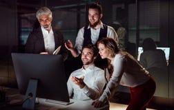 Een groep bedrijfsmensen in een bureau bij nacht, die computer met behulp van royalty-vrije stock foto