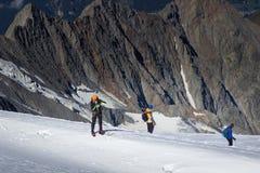 Een groep bergbeklimmers beklimt tot de bovenkant van een snow-capped berg stock foto's