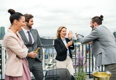 Een groep blij zakenlui die een partij in openlucht op dakterras hebben in stad stock fotografie