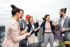Een groep blij zakenlui die een partij in openlucht op dakterras hebben in stad royalty-vrije stock afbeeldingen