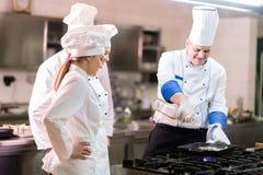 Een groep chef-koks die heerlijke maaltijd in hoog luxerestaurant voorbereiden royalty-vrije stock afbeeldingen