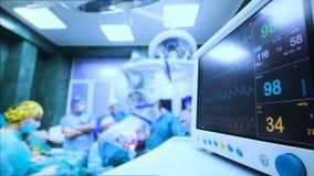Een groep chirurgen werkt op de de levensfunctiesmonitor van de pati?nt stock videobeelden