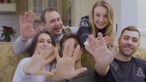 Een groep de Kaukasische handen van vrienden gelukkig golven aan camera stock videobeelden