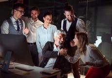 Een groep die bedrijfsmensen met computer in een bureau, opwinding uitdrukt stock afbeeldingen