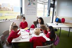 Een groep die de jonge geitjes van de zuigelingsschool bij een lijst in een klaslokaal met hun vrouwelijke leraar zitten royalty-vrije stock fotografie