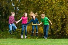 Een groep die jonge geitjes in de lucht springt Stock Foto's