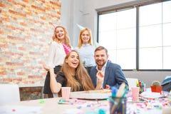 Een groep die mannen en vrouwen die in het bureau werken, pizza in een feestelijke stemming eten stock foto