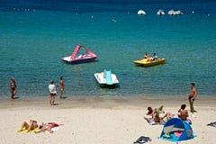 Een groep die mensen op een zandig strand voor het overzees ontspannen stock afbeeldingen