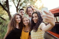 Een groep die vrienden met smartphone op een roadtrip door platteland, selfie nemen royalty-vrije stock fotografie