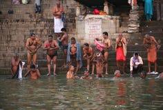 Een groep Indische mensen die vóór Ganges wassen Stock Foto