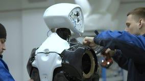 Een groep ingenieurs creeert een moderne robot of androïde Controle en reparatie gebroken punten Vervaardiging en vervaardiging v stock videobeelden