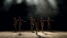 Een groep jonge ballerinameisjes die op stadium in dark dansen, close-up Langzame mo stock footage