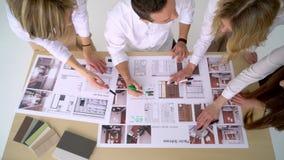 Een groep jonge die ontwerpers door het hoofd worden geleid werkt aan het project van ontwerp commercieel centrum, woonhuis, stud stock videobeelden