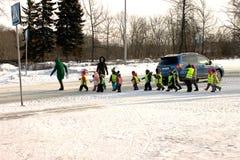 Een groep jonge kinderen onder de supervisie van verzorgers kruist de weg royalty-vrije stock afbeeldingen