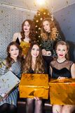 Een groep jonge mooie vrouwen viert het nieuwe jaar, Kerstmis Confettien, giftdoos, positieve emoties stock foto's