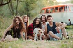 Een groep jonge vrienden met een hondzitting op gras op een roadtrip door platteland royalty-vrije stock foto's
