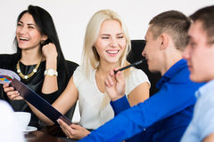 Een groep jonge vrolijke mensen in een vergadering bij bureauzitting Royalty-vrije Stock Afbeelding