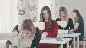 Een groep jonge vrouwen bij het naaien van cursussen: het snijden en het naaien stock footage
