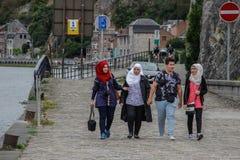 Een groep jongeren, één kerel en verscheidene Moslimmeisjes in hijabs lopen en lachen op een stadsstraat stock fotografie
