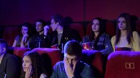 Een groep jongeren die op een droevige film in de bioskoop letten, het meisje schreeuwt stock videobeelden