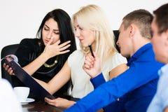 Een groep jongeren in een vergadering bij bureauzitting Stock Afbeeldingen