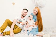 Een groep jongeren, een familie van vader en moeder 30 jaar en een dochter van één jaar, huizen in een licht binnenland zit op ee Royalty-vrije Stock Afbeeldingen