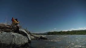 Een groep kerels, de kerels en de meisjes zitten op de bank van een bergrivier stock videobeelden