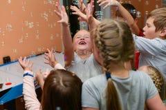 Een groep kinderen die met zeepbels spelen royalty-vrije stock foto's