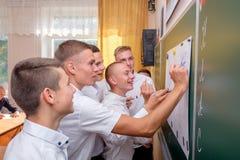 Een groep klasgenoten trekt op een bord met een viltpen stock foto