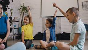 Een groep lage schoolkinderen heft hun handen op om de vraag van de leraarss pret te beantwoorden Groep leerlingen met omhoog han stock footage