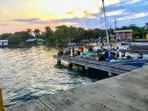 Een groep lokale visser Van Belize keert hun boot naar het dok na een dag van visserij terug als zonreeksen royalty-vrije stock foto