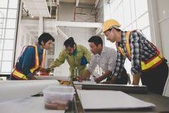 Een groep mannelijke en vrouwelijke ingenieurs komt om over p te spreken samen stock foto