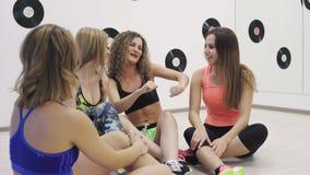 Een groep meisjes die op de vloer in de geschiktheidsruimte zitten, mededeling, glimlach, ontspant stock video