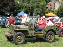 Een groep mensen in een uitstekende militaire jeep wordt gezeten en anderen die uitstekende auto's bekijken bij hebden openbare v Royalty-vrije Stock Foto's