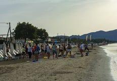 Een groep mensen voert lichaamsbewegingen op het strand uit Stock Fotografie