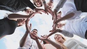 Een groep middelbare schoolstudenten kijkt door de vorm van een cirkel van hun palmen wordt gecreeerd die Het concept vriendschap royalty-vrije stock afbeeldingen