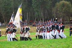 Een groep militair-reenactors maart met een vlag Stock Foto's