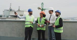 Een groep multi-etnische arbeiders bij de architecten en de voorman die van de bouwwerfingenieur het plan van bouw analyseren stock videobeelden