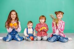 Een groep pretkinderen speelt in de ruimte Nuttige vruchten Stock Foto's