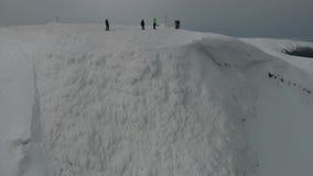 Een groep snowboarders bevindt zich bovenop een berg dichtbij een sneeuwberg stock footage