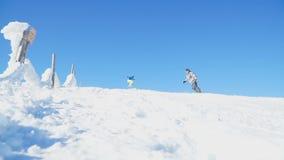 Een groep snowboarders voert hoge snelheidssprongen op een snow-covered helling in de Karpaten uit stock footage