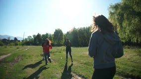 Een groep sportenjongeren voert openluchtsporten onder de groene aard in de bergen uit stock video