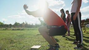 Een groep sportenjongeren voert openluchtsporten onder de groene aard in de bergen uit stock videobeelden