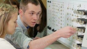 Een groep studenten die aan een proefbank Fysiek Laboratorium samenwerken Vele schakelaars en lichten De mannen en de vrouwen sch stock video