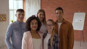 Een groep studenten van 5 mensen is internationaal pret succesvolle kerels in het klaslokaal de leerlingen benadrukken de vinger stock footage