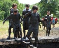 Een groep tienerjaren probeert om een hindernis tijdens de Mankato-gebeurtenis van de Modderlooppas te navigeren Stock Foto's