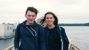 Een groep tieners loopt langs de brug van de rivier stock videobeelden