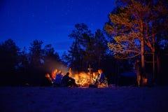 Een groep toeristen die het kampvuur rondhangen bij nacht Stock Foto's