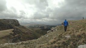 Een groep toeristen drie mensen loopt hoog in bewolkt weer op de rand van het plateau in de bergen Langzame Motie stock videobeelden